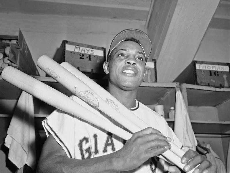 Willie Mays holding bats in the clubhouse