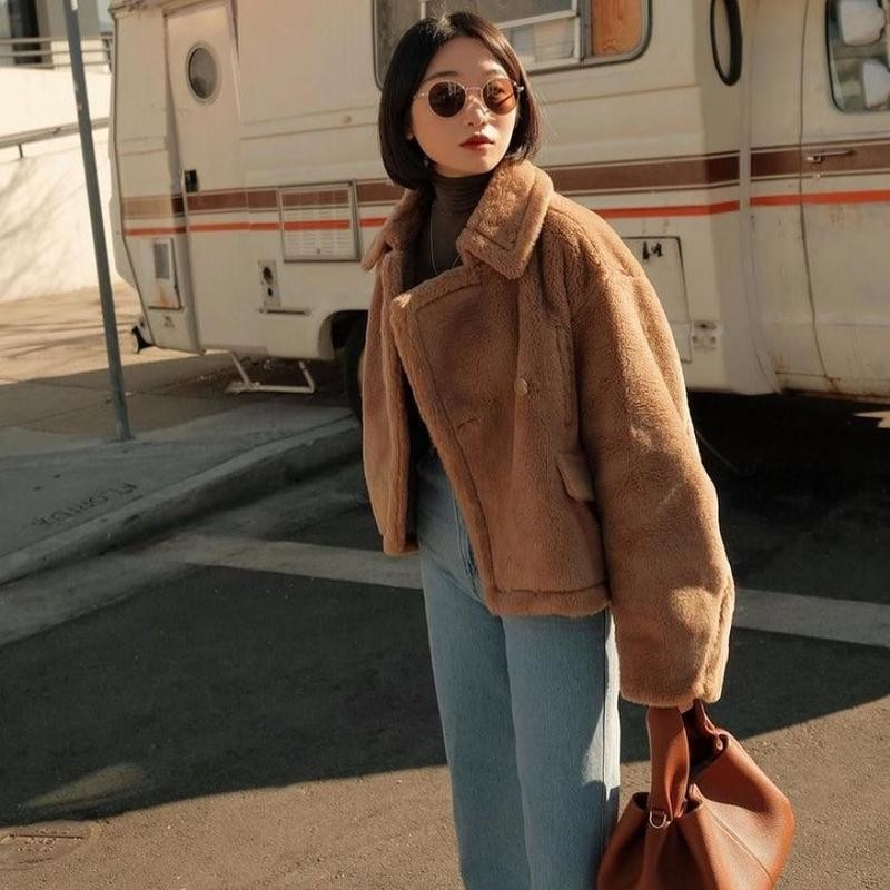 Woman posing in jacket in front of RV