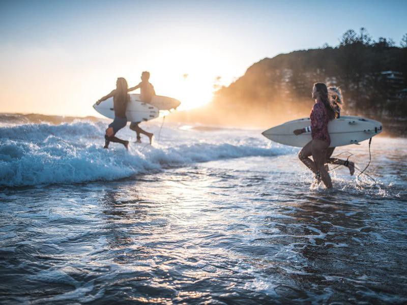 Friends running into the ocean with their surfboards in Australia