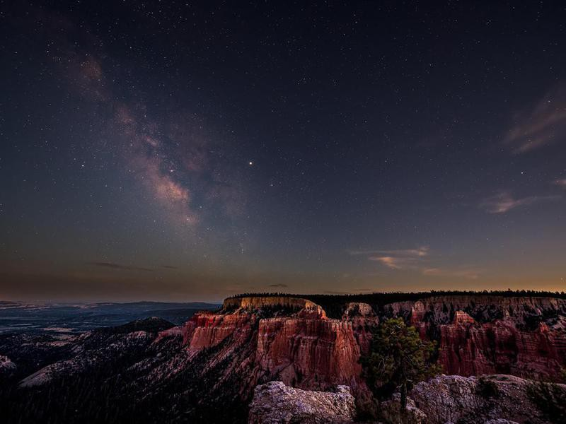 Night sky with dark milky way starscape in Bryce Canyon National Park in Utah at Pariah view overlook and rock formations panoramic viewpoint