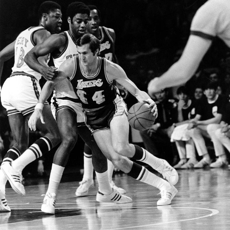 Jerry West drives around Milwaukee Bucks guard Oscar Robertson and Curtis Perry