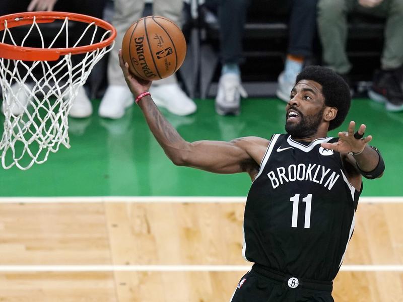 Brooklyn Nets guard Kyrie Irving scores against Boston Celtics