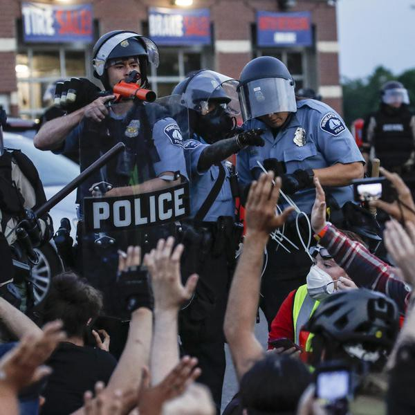A police officer points a hand cannon at protesters who have been detained pending arrest on South Washington Street, Sunday, May 31, 2020, in Minneapolis. Protests continued following the death of George Floyd, who died after being restrained by Minneapolis police officers on Memorial Day. (AP Photo/John Minchillo)