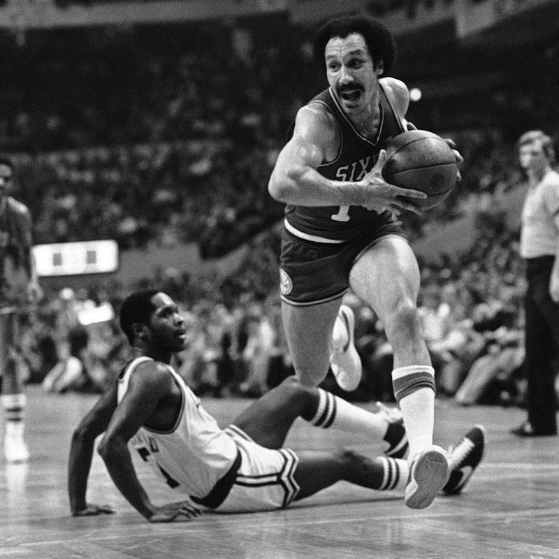 Henry Bibby leaps over Nate Archibald of Boston Celtics