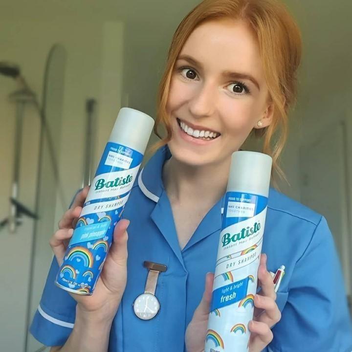 Woman holding up Batiste Dry Shampoo