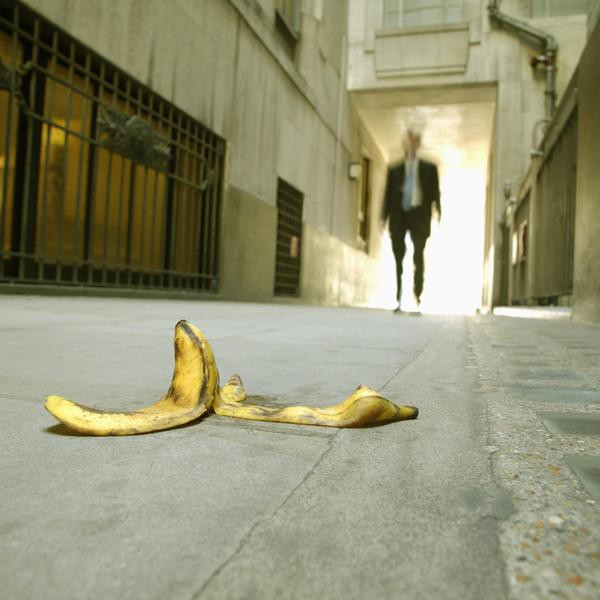 Low angle view of a businessman walking towards a banana skin themes of careless problems risk safety