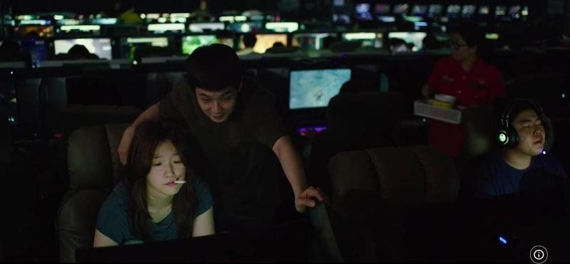 Choi Woo-sik and Park So-dam looking at screen in Parasite