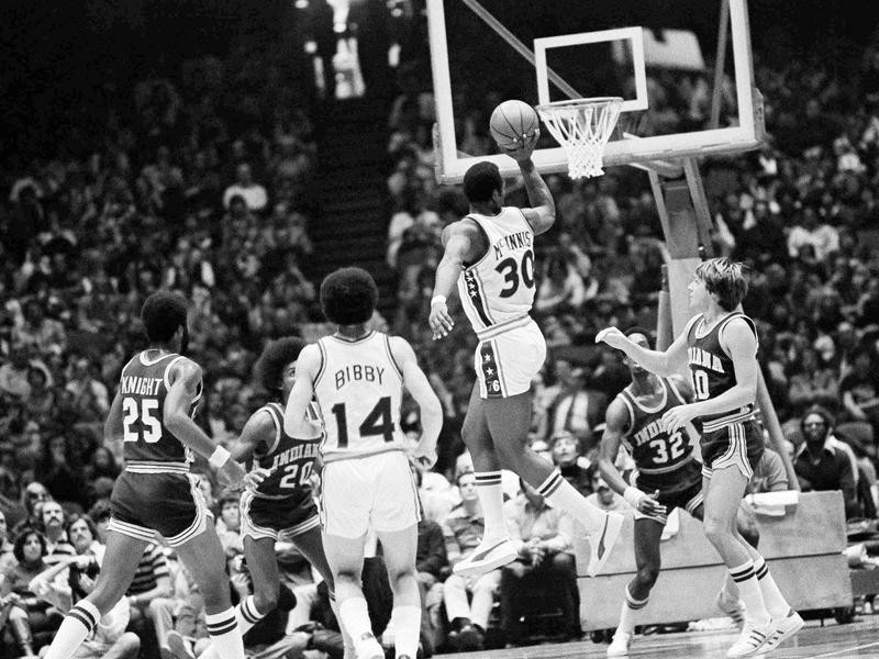 George McGinnis goes by Indiana Pacer's Don Buse for one-handed shot