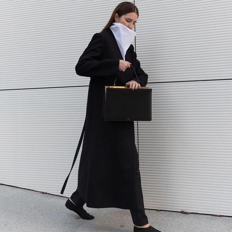 Woman walking in long black jacket
