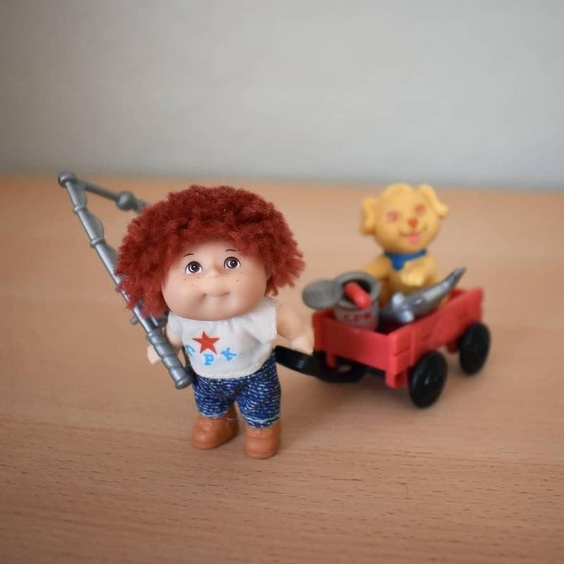 Cabbage Patch Kids mini carrying a wagon with a dog