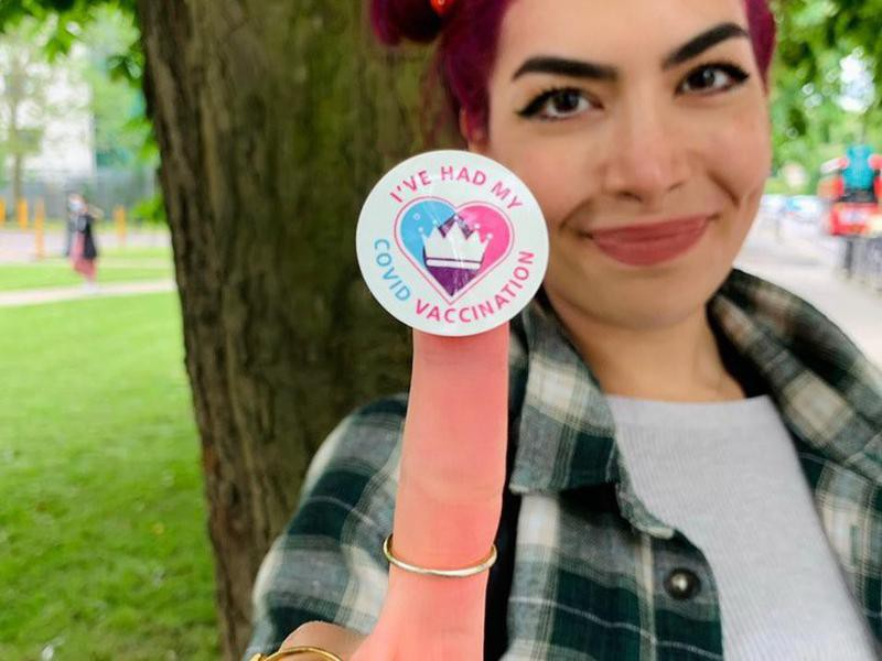 Woman Holding Up Covid Vaccination Sticker