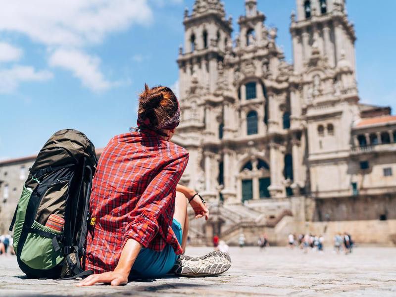Woman backpacker siting on the Obradeiro square (plaza) in Santiago de Compostela