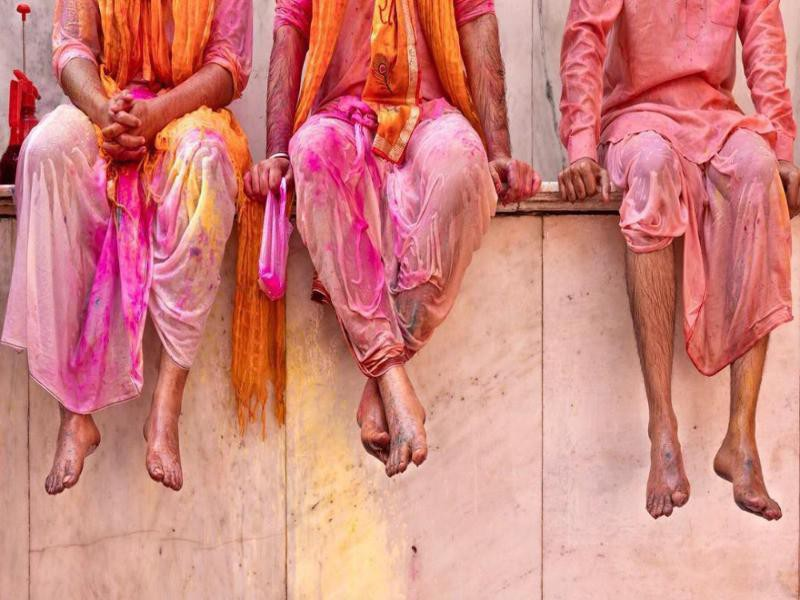 Men sitting on wall during Holi