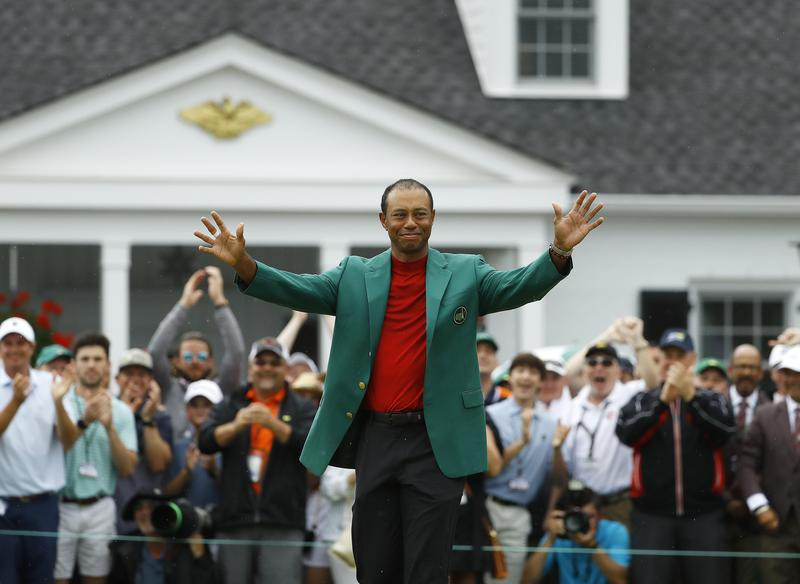 Tiger Woods smiles as he wears his green jacket after winning the Masters golf tournament
