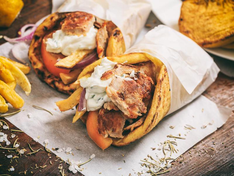 Greek gyros wrapped in a pita bread on a wooden background