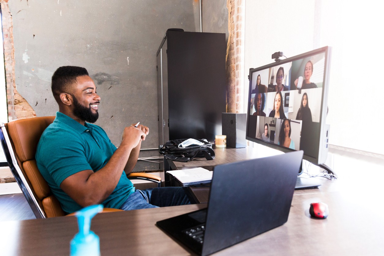 Cheerful businessman video chats with colleagues
