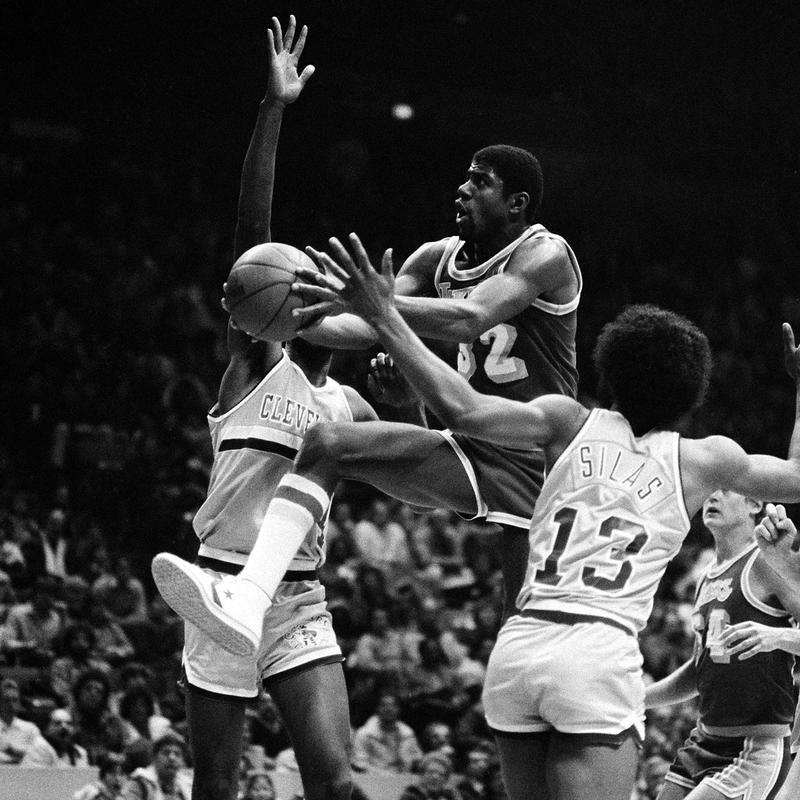 """Earvin """"Magic"""" Johnson flies between Cleveland Cavalier defenders"""