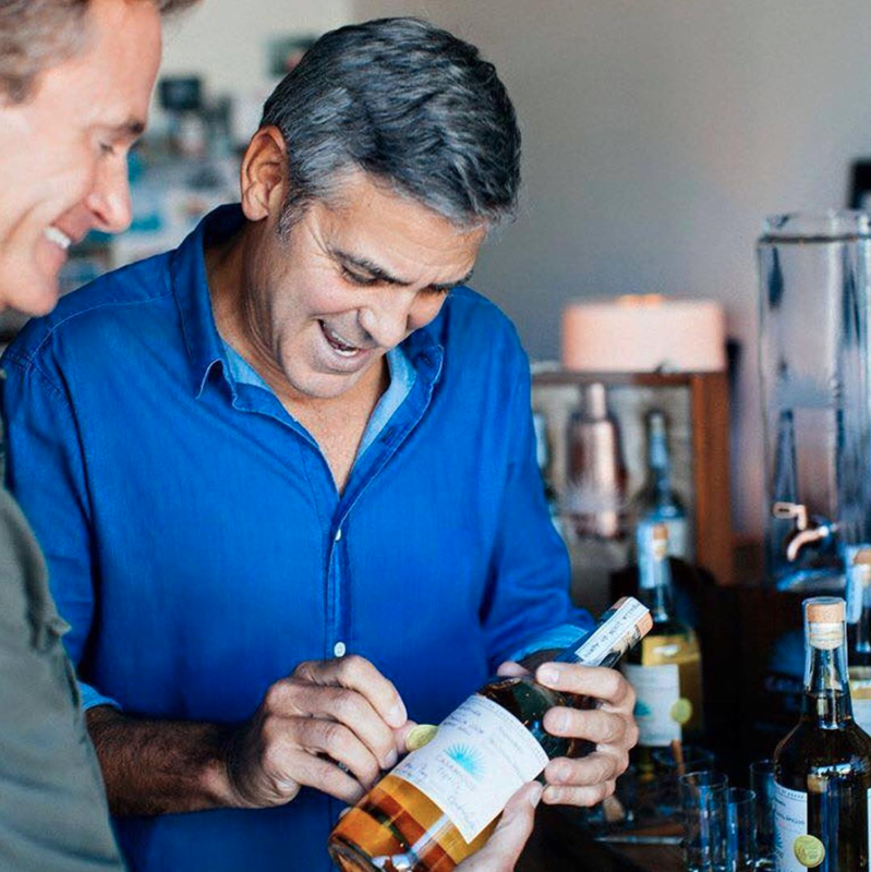 George Clooney signs a bottle of Casamigos tequila.