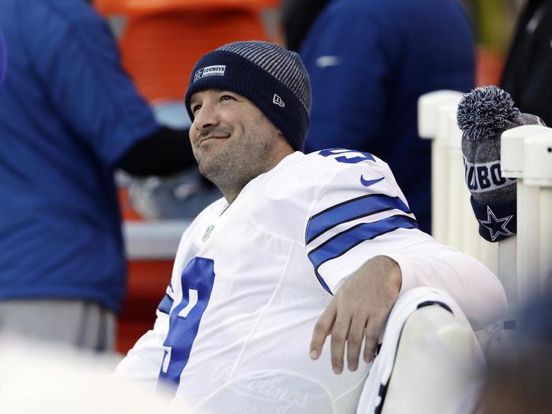 Tony Romo of Dallas Cowboys smiles on bench