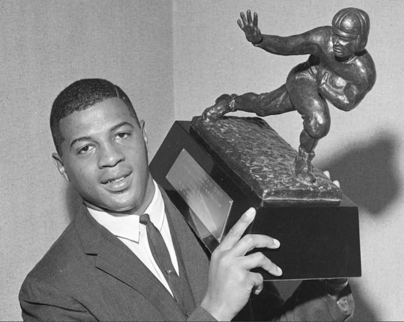 Ernie Davis holding up Heisman Trophy