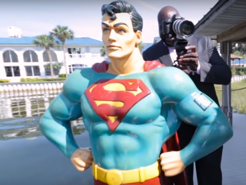 Shaq on his dock with a statue of Superman