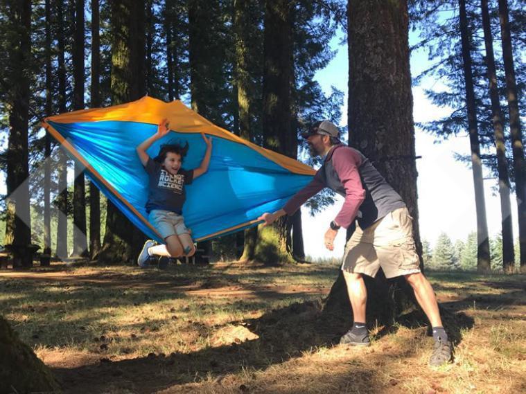 Dad swinging boy in parachute hammock