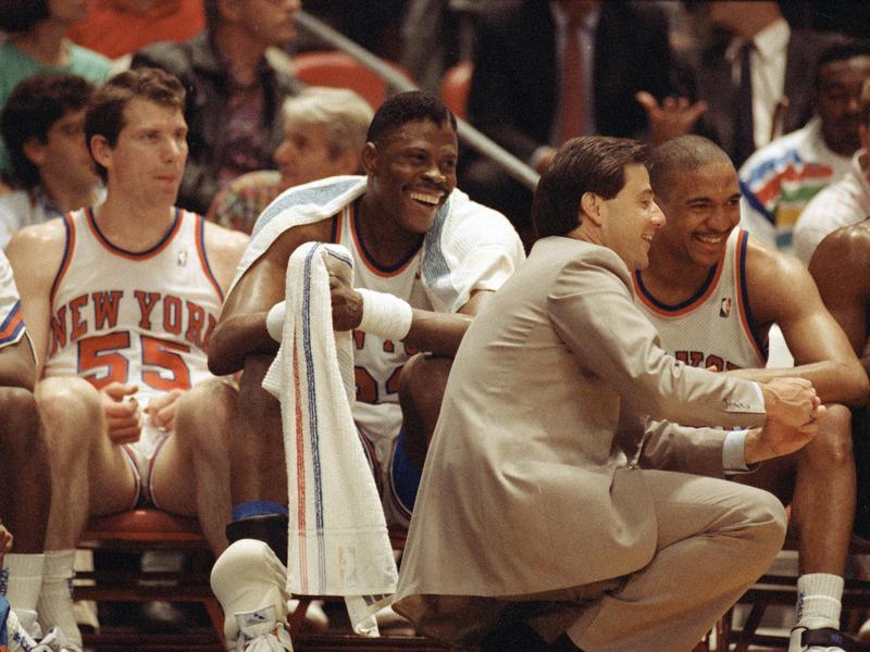 Kiki Vandeweghe, Patrick Ewing, and Mark Jackson laugh on bench