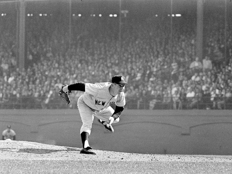 New York Yankees Whitey Ford twists himself as he delivers pitch