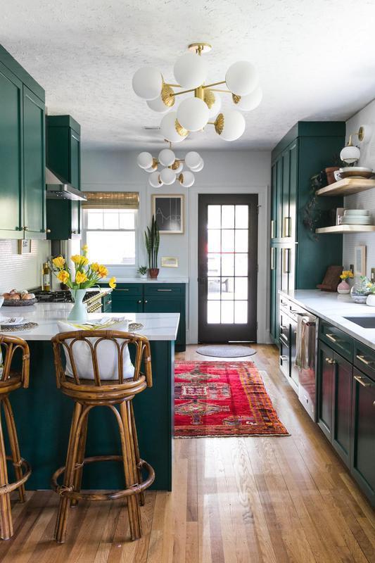 Deep green kitchen with Art Deco light fixtures