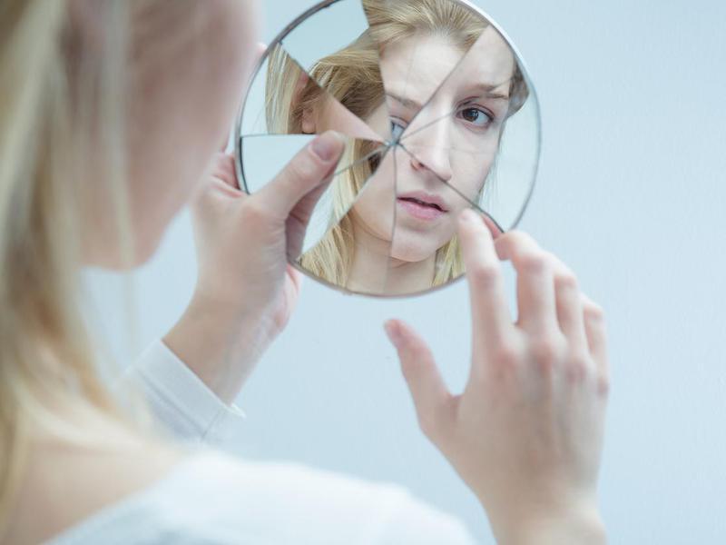 Woman looking into broken mirror