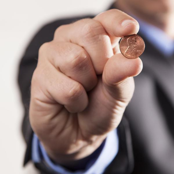 A businessman holds up a penny on a white background showing savings and earnings.
