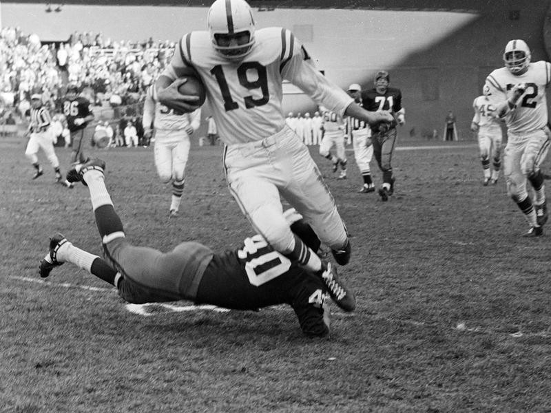 Johnny Unitas runs past Washington Redskins