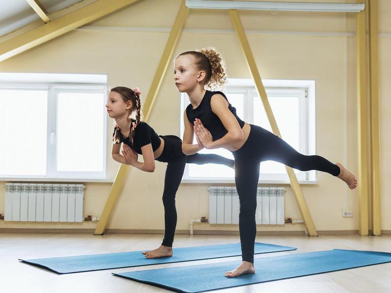 Two little girls practicing yoga, performing virabhadrasana exercise, warrior pose 3
