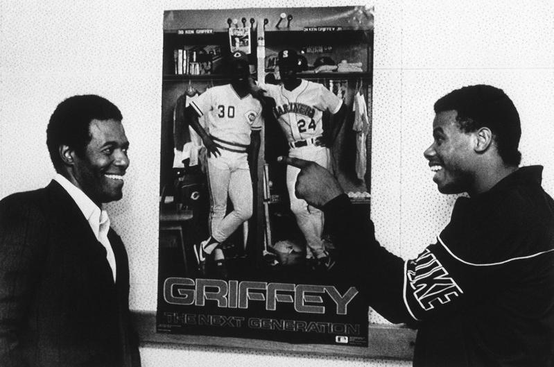 Ken Griffey Sr. and Ken Griffey Jr. joke around by poster in Cincinnati