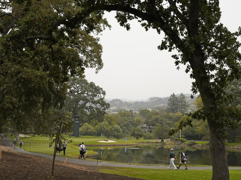 Tom Kim walks with his caddie to 11th green
