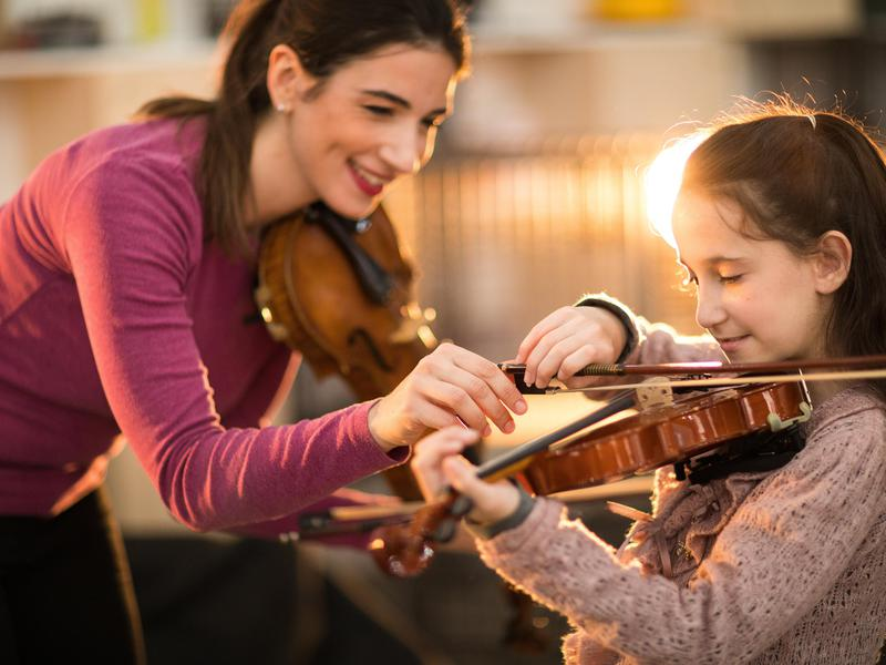 Woman giving violin lesson to kid
