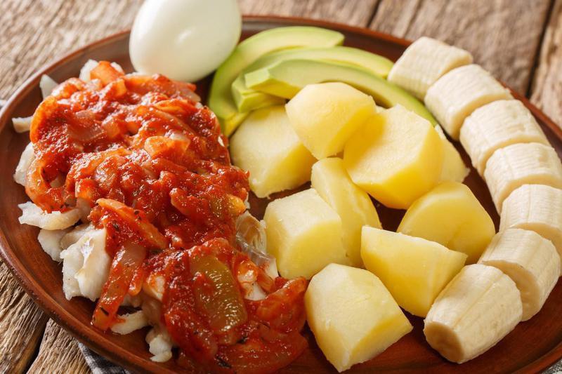 Bermuda codfish breakfast with onion tomato sauce, boiled potatoes, eggs, banana and avocado close-up in a plate. horizontal