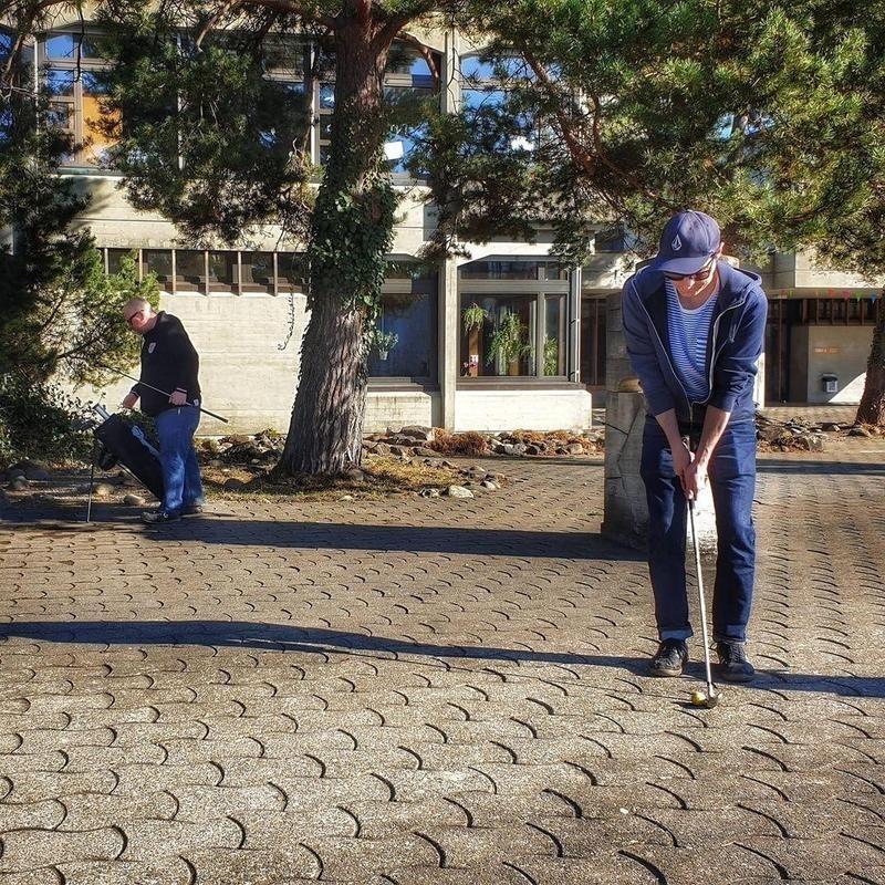Man urban golfing on cobblestone