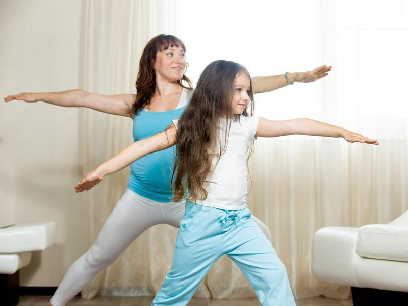 Mother and daughter doing warrior 2 pose