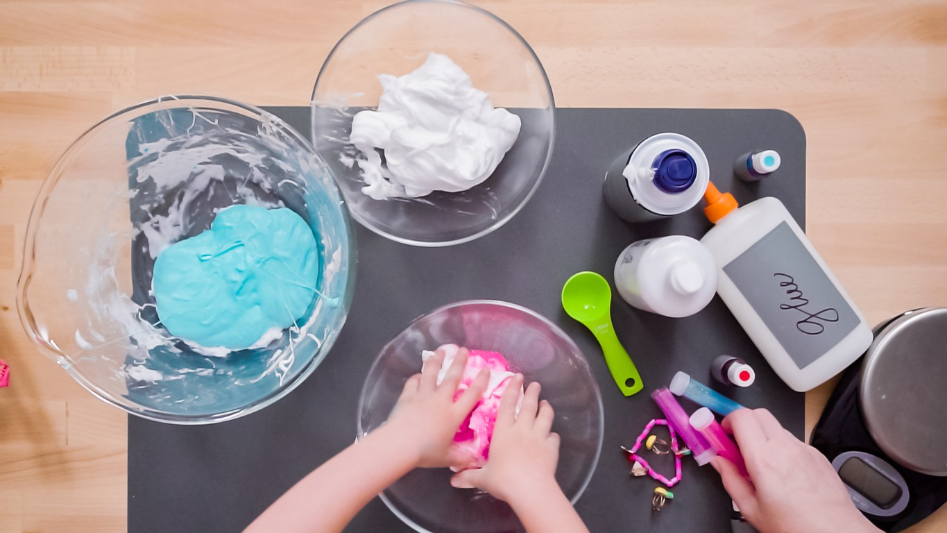 Mother and daughter making colorful fluffy slime