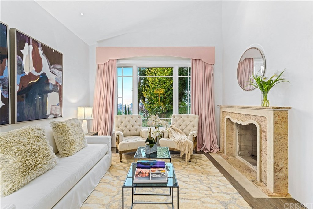 Living room with pink drapes and fireplace