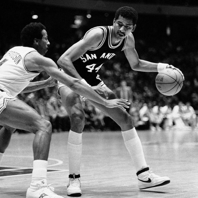 San Antonio Spurs' George Gervin tries to dribble around guard