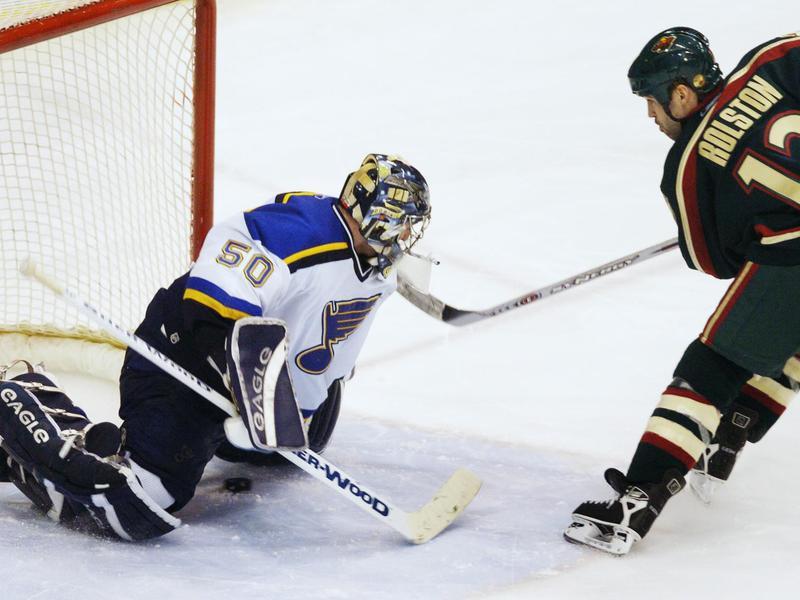 Minnesota Wild's Brian Rolston slides puck under St. Louis Blues goalie Reinhard Divis