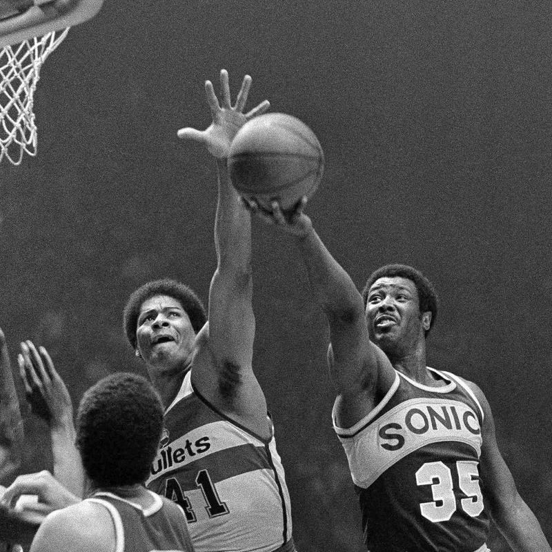 Washington Bullets' Wes Unseld reaches to block shot by Seattle Supersonics' Paul Silas