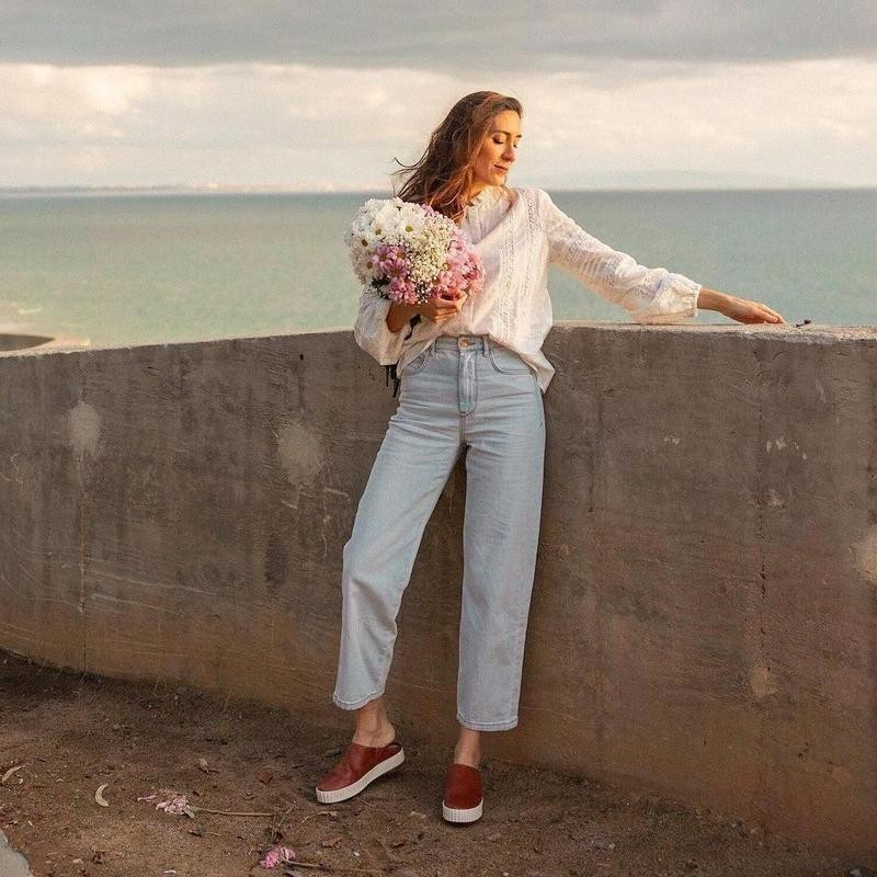Woman in jeans with flowers by water
