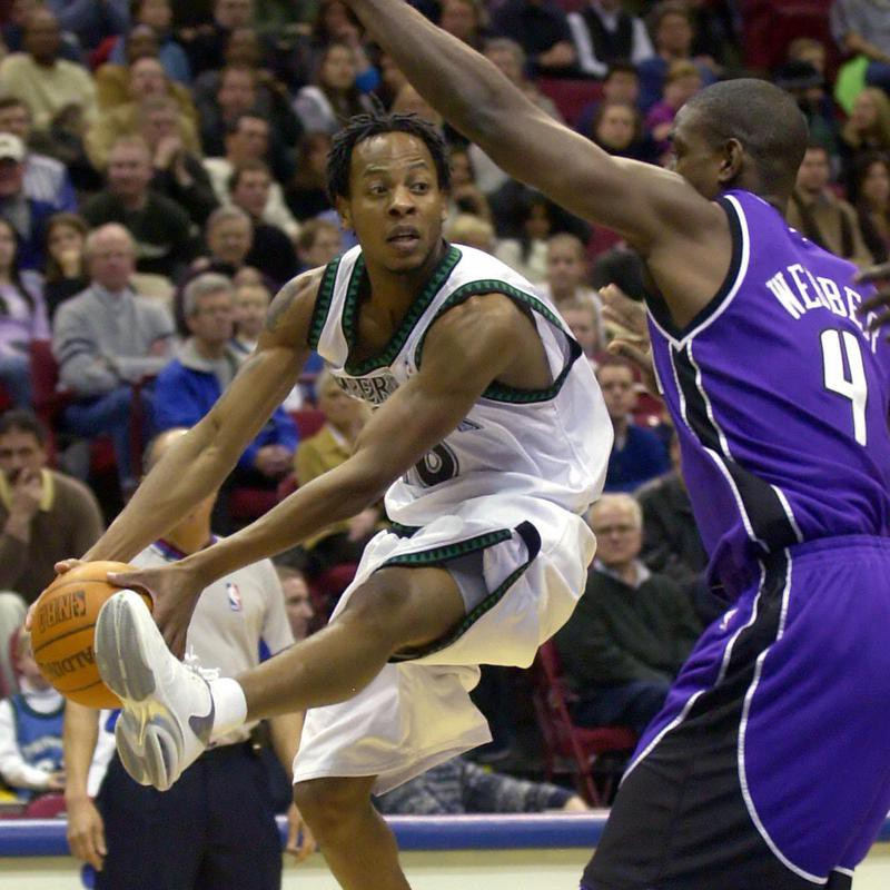 Troy Hudson looks to pass around Sacramento Kings forward Chris Webber
