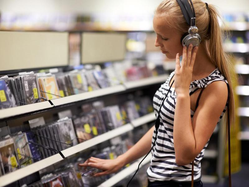 young woman listening to music on headphones at the store