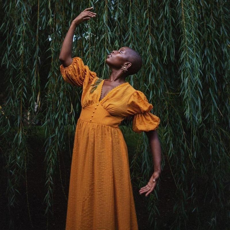Woman in mustard dress posing