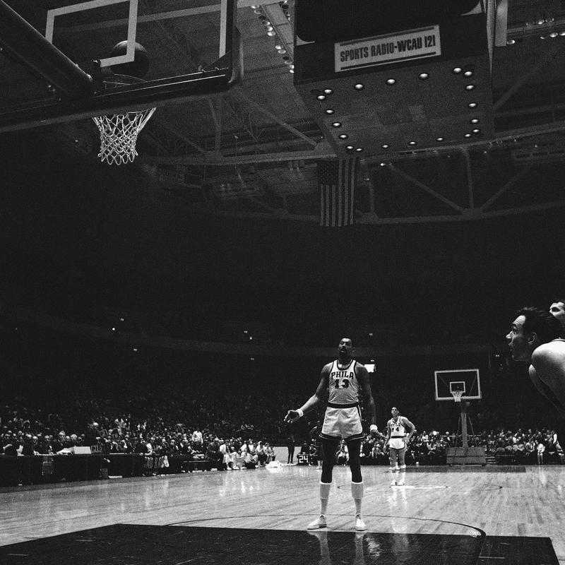 Wilt Chamberlain watches his basket