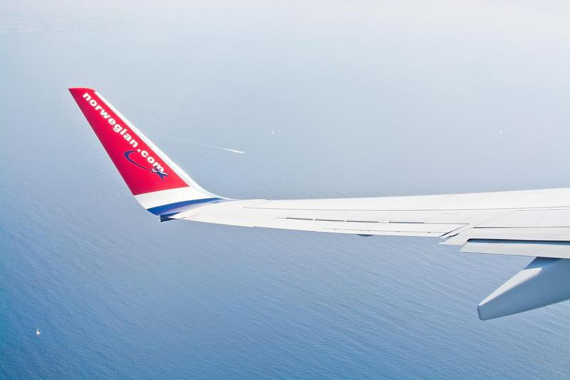 Norwegian wing over the Mediterranean sea with boats